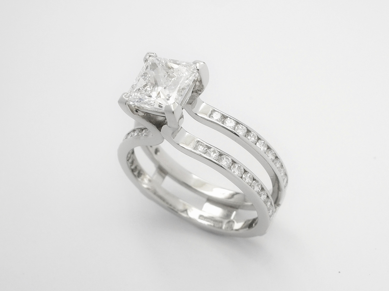 Single stone 1.19ct.'D' colour princess cut diamond 'Embrace' ring set in platinum with round brilliant cut diamonds set in twin shanks. View with wedding ring in shaped wedding ring