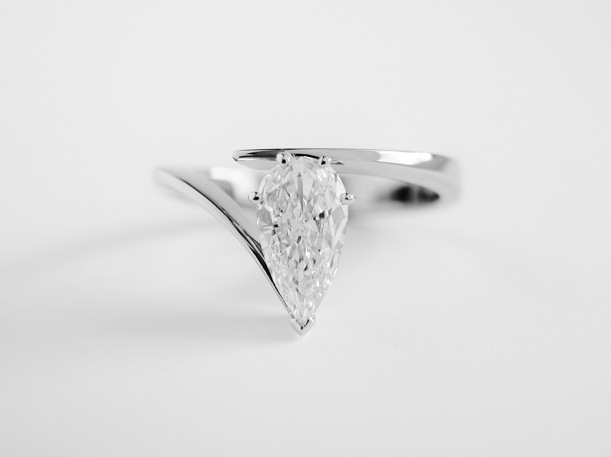 Single stone 0.74ct 'E' colour Pear shaped diamond set in a straight wishbone cross-over platinum ring mount. Ideal diamond sizes from 0.33ct to 3.00cts.