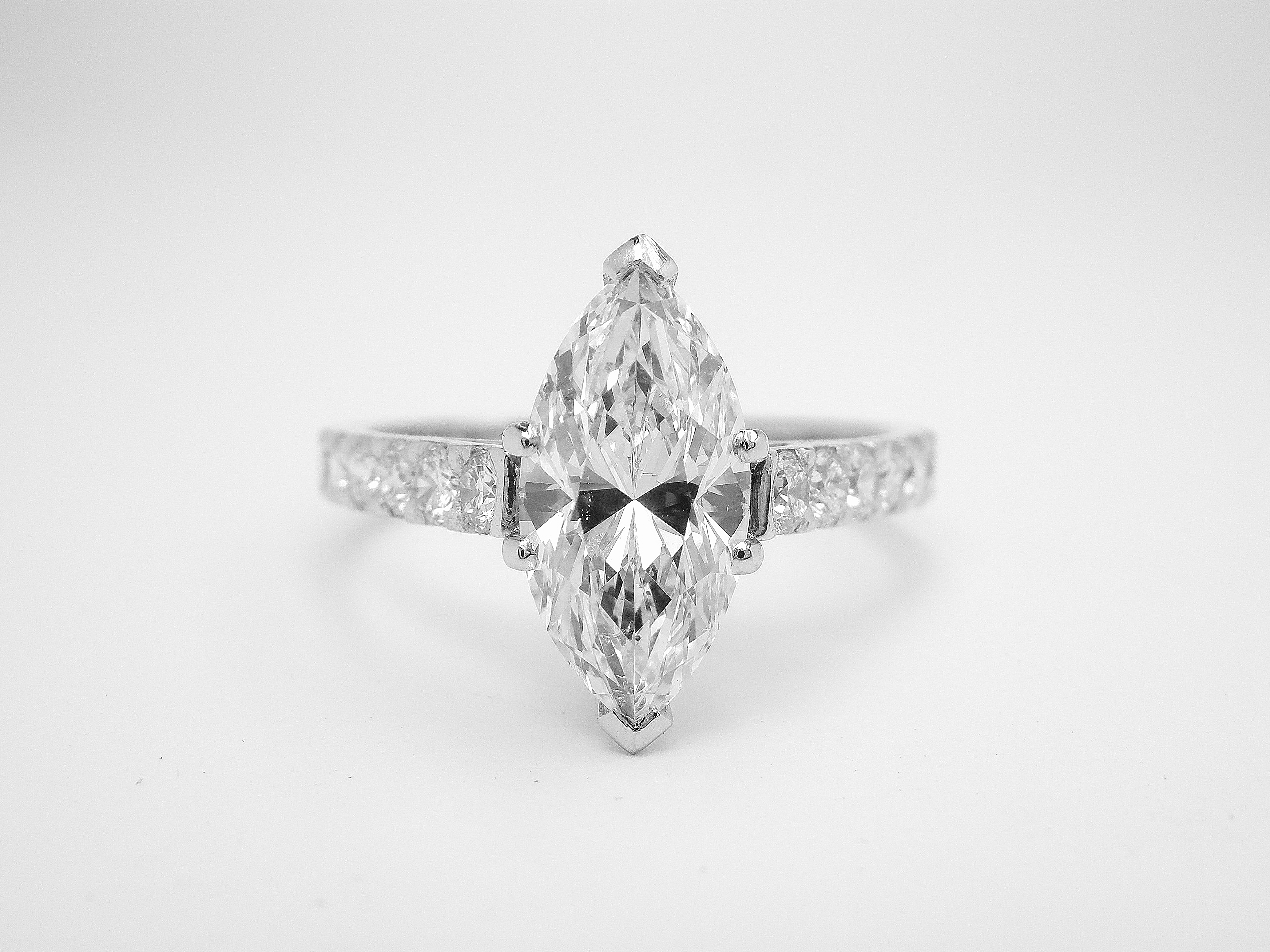 Platinum single stone 1.51ct. 'D' colour Marquise diamond ring with round brilliant cut diamonds cut down set in shoulders.