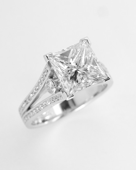 A 2.01ct. 'G' colour Princess cut diamond mounted in a split shoulder platinum ring mount with small round brilliant cut diamonds channel set in shoulders. Ideal diamond size 1.5ct to 5ct