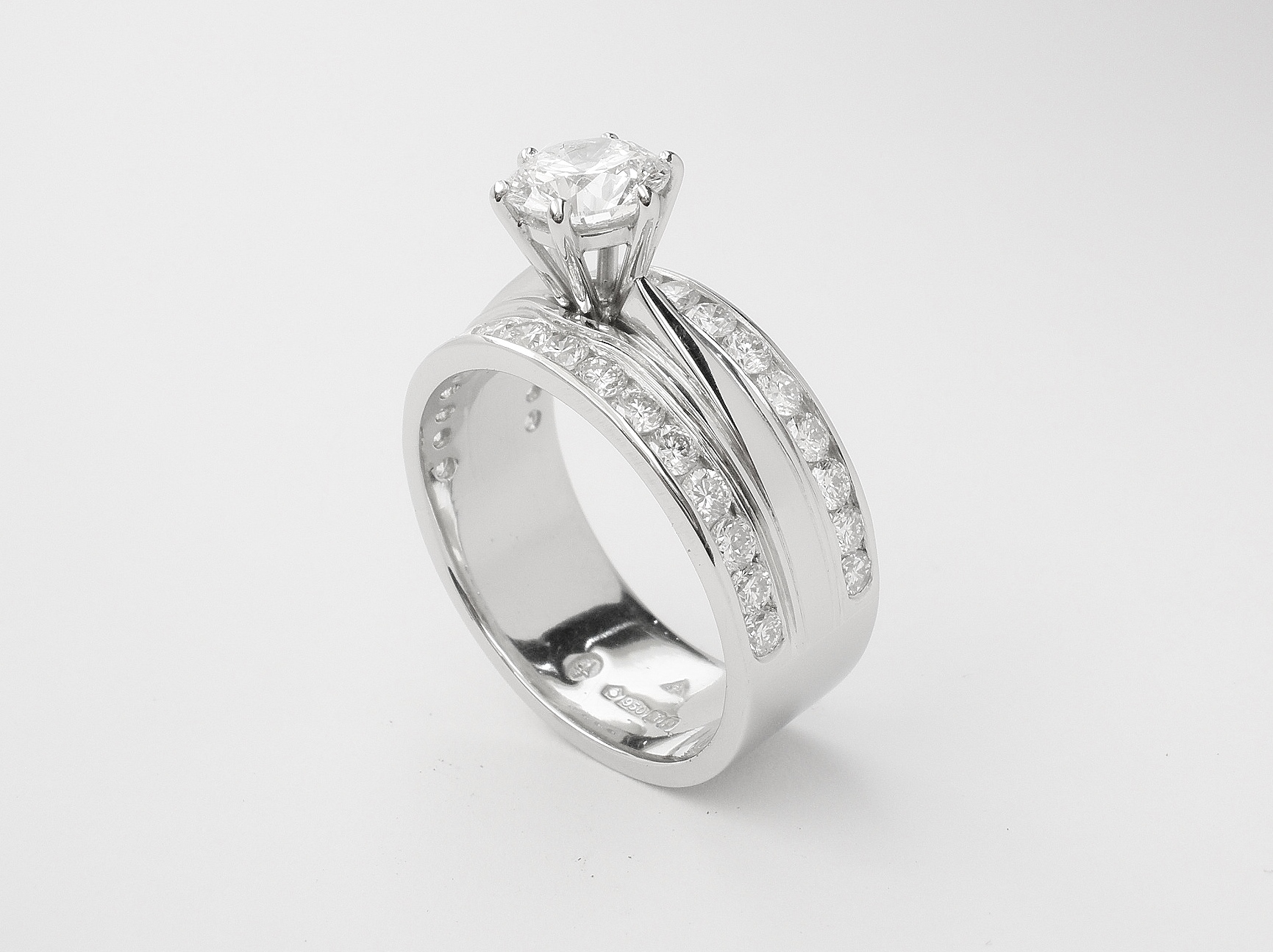 A round brilliant cut 0.91ct. 'F' colour diamond mounted in a broad platinum one piece engagement and wedding ring with round brilliants channel set across the top edges.