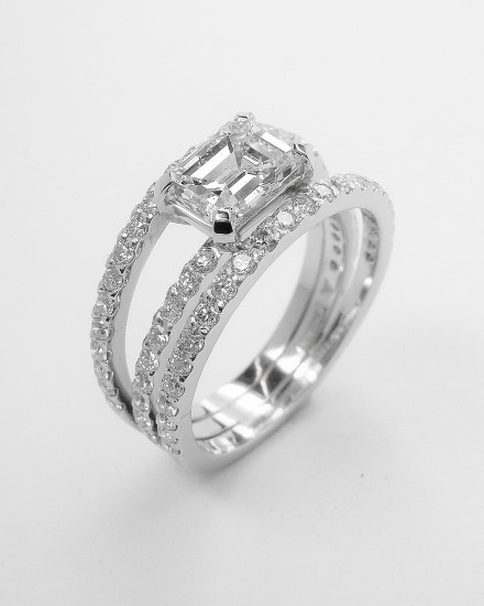 An Emerald cut 1.03ct. diamond of 'E' colour, platinum set on a triple banded ring with cut down brilliant cut diamonds. Ideal diamond sizes 0.75ct. to 1.50ct.
