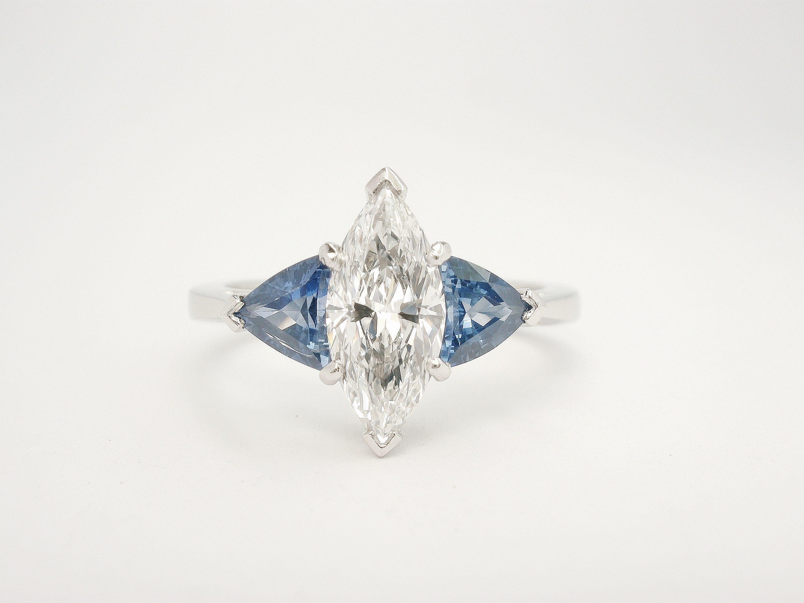 A 3 stone Marquise diamond and trilliant shaped sapphire ring mounted in platinum.