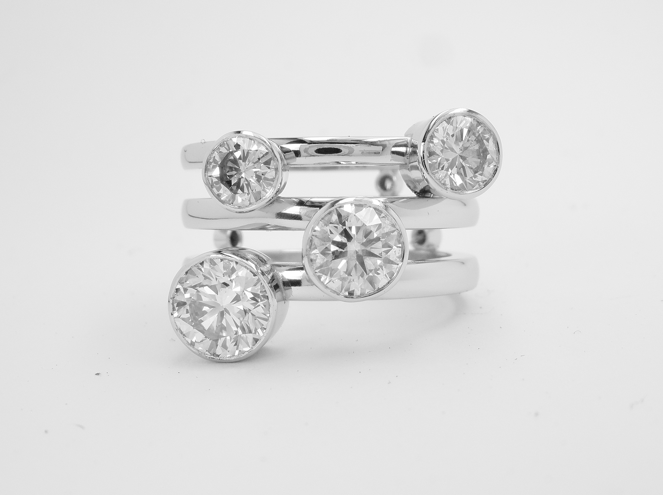 Round brilliant cut diamond 4 stone bezel set (rub-over set) ring with a triple parallel banded ring shank set with small diamonds on reverse side of bands.