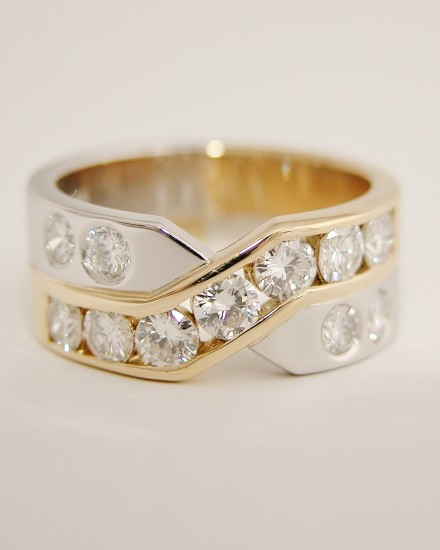 Platinum & 18ct. yellow gold 'X' style ring with 7 round brilliant cut diamonds channel set in the 18ct. yellow gold cross-over panel & 4 flush set diamonds in the platinum.