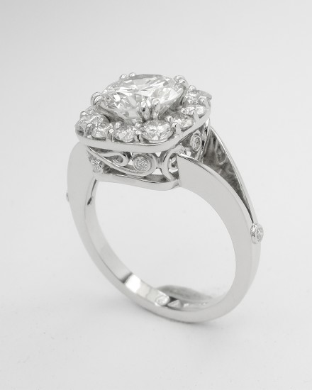 Cushion shaped diamond cluster platinum ring with split shoulder created from 13 round brilliant cut diamonds & diamond set scroll effect round the setting sides. Centre stone 1.90ct 'G' colour.