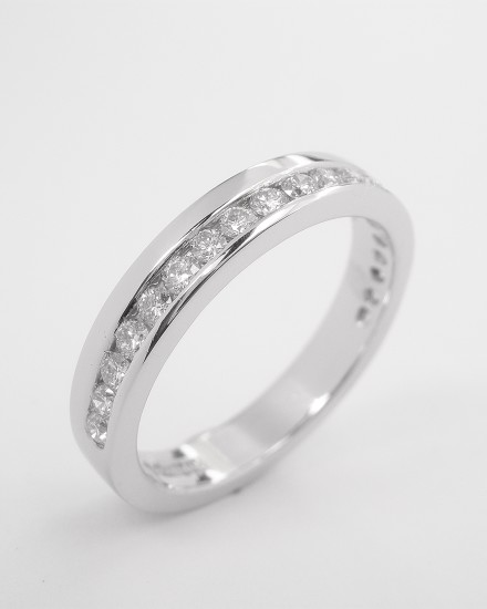 Platinum offset round brilliant cut diamond wedding ring.