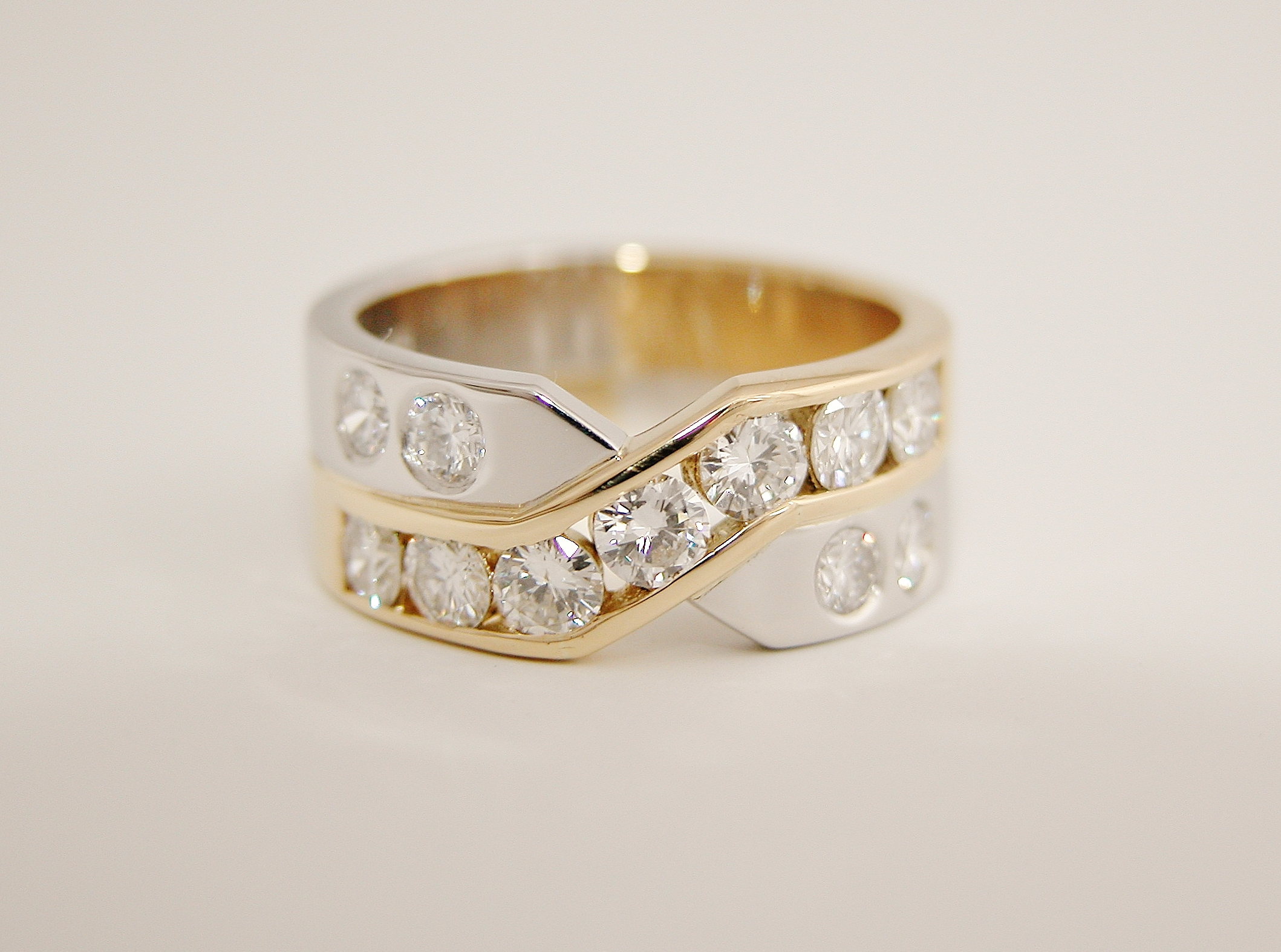 Platinum & 18ct. yellow gold 11 stone channel and flush set diamond cross over style ring.