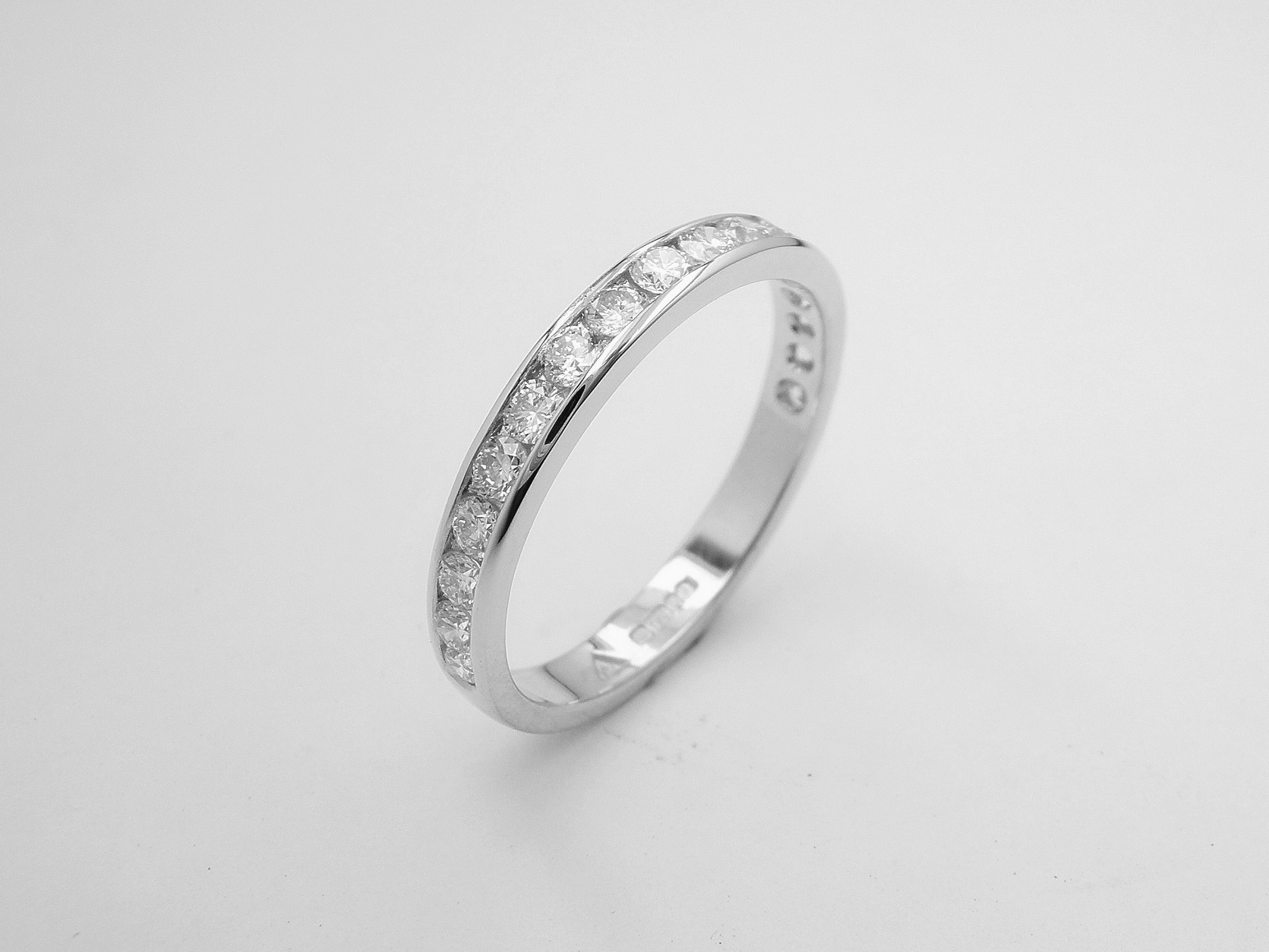 Platinum & channel set round brilliant cut diamond wedding ring set to 55% cover.