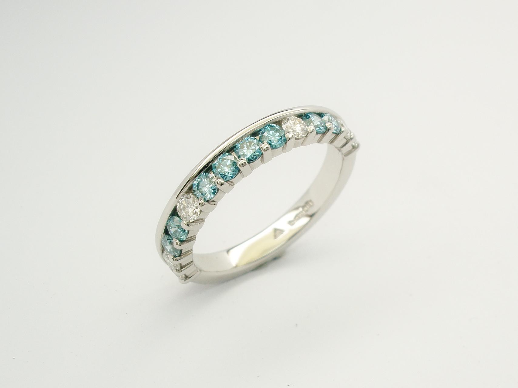 Platinum part channel set round brilliant cut sky blue diamond & white diamond wedding ring set to 55% cover.