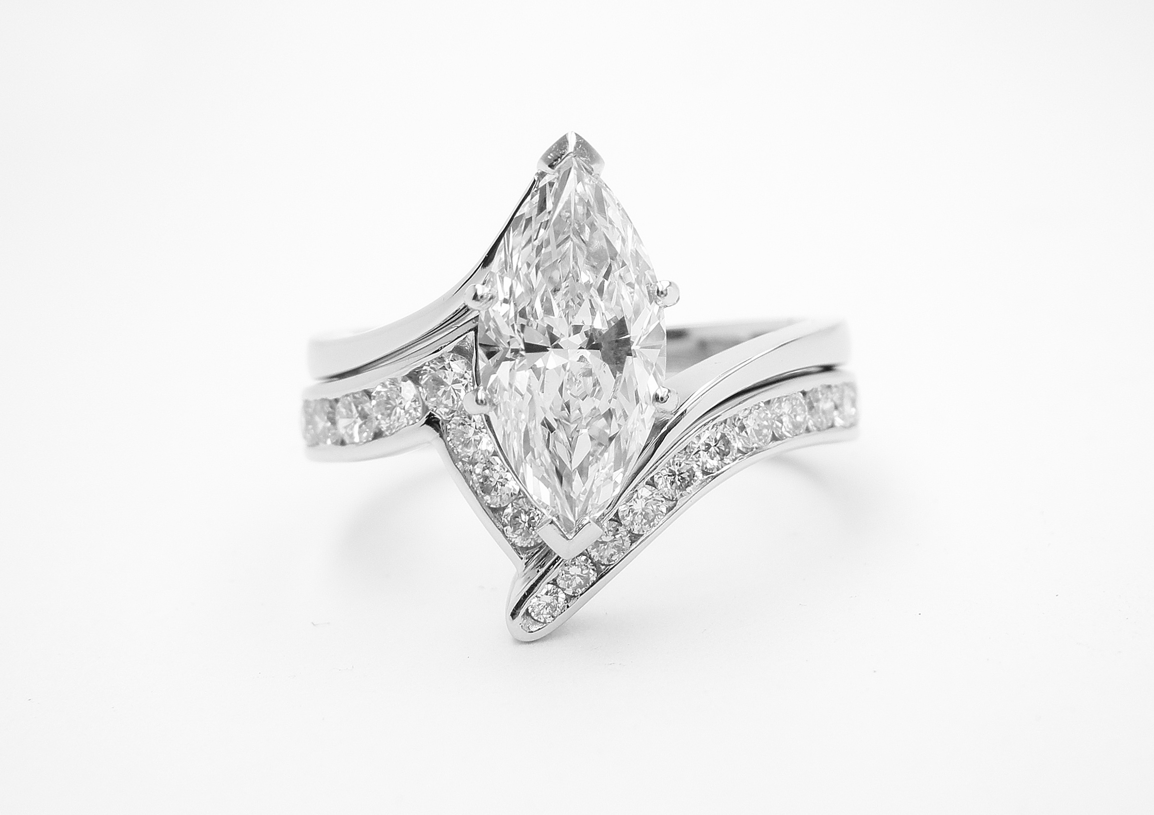 Platinum zig-zag wedding ring shaped to fit around a single stone marquise cross-over engagement ring and channel set with round brilliant cut diamonds to 55% cover.