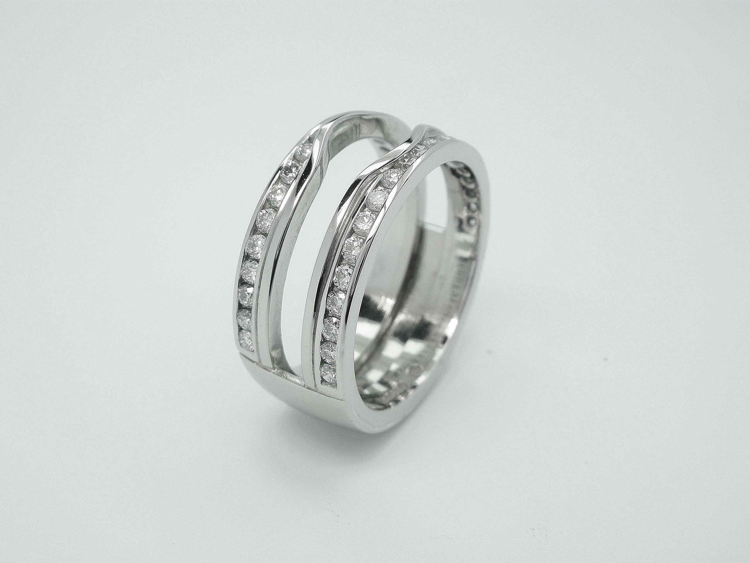 Double 'Embrace' platinum wedding ring channel set with round brilliant diamonds & created to receive the insertion of a single stone round diamond engagement ring.