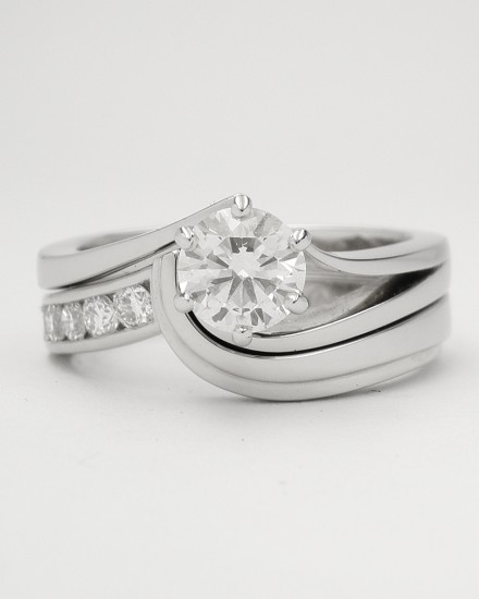 Palladium shaped wedding ring with channel set diamonds on one side & shaped to fit with a single stone diamond open shouldered wishbone cross-over ring.