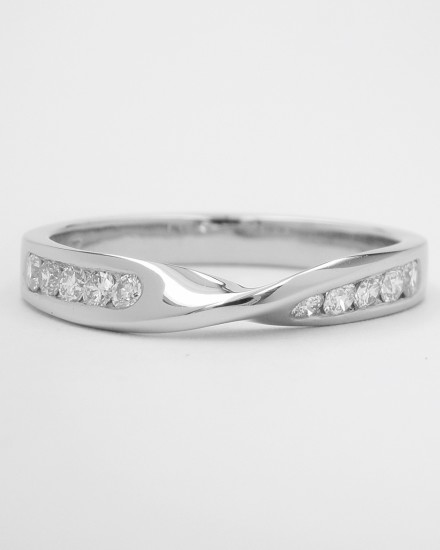 Diamond set 'twist' palladium wedding ring shaped to fit with a single stone diamond ring with pear diamond shoulders. This will fit with a single stone ring.