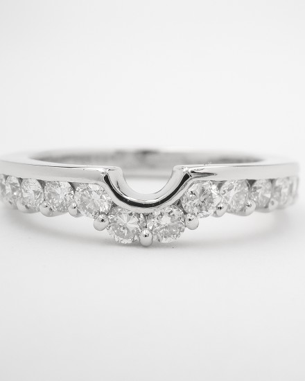 Part channel set platinum wedding ring shaped to fit with a single stone round diamond engagement ring.