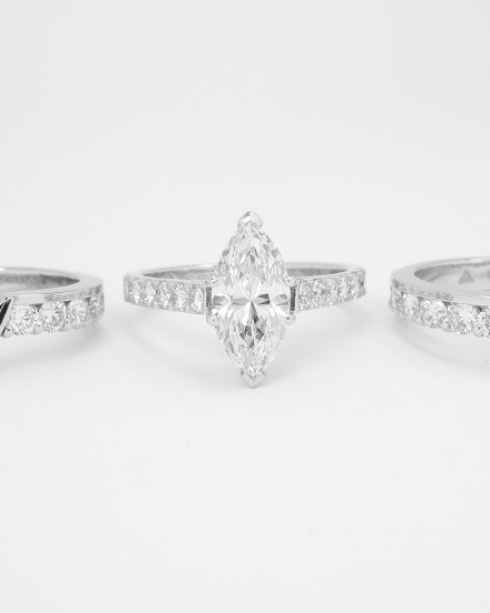 A pair of twin platinum part channel set diamond wedding rings shaped to fit with a single stone straight marquise shaped diamond engagement ring.