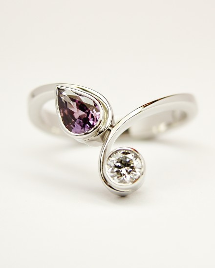 Pear shaped purple sapphire and round brilliant cut diamond rub-over set 2 stone curly wishbone style ring mounted in palladium & platinum.