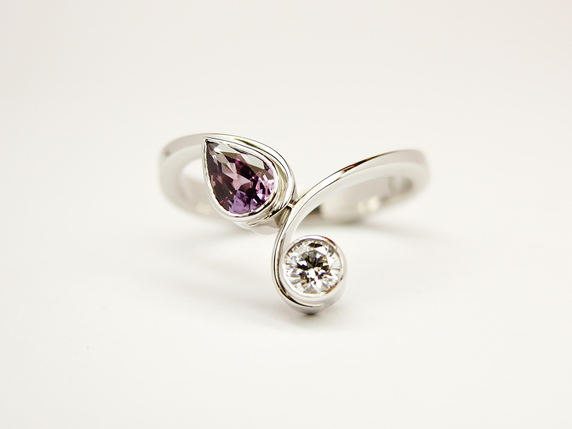 Pear shaped purple sapphire and round brilliant cut diamond rub-over set 2 stone curly wishbone style ring mounted in palladium & platinum.