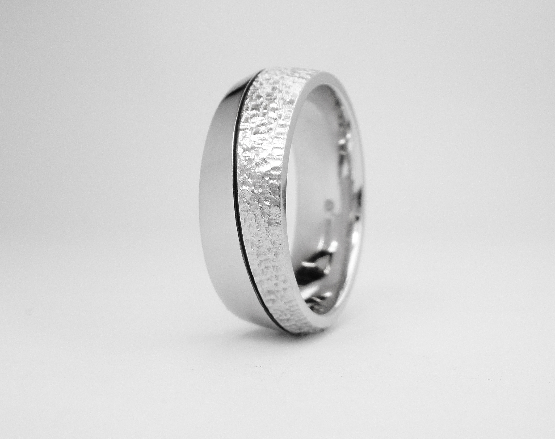 Palladium flat 'V' sectioned gents wedding ring with darkened orbital line cut, polished finish one side & rough texture on other.