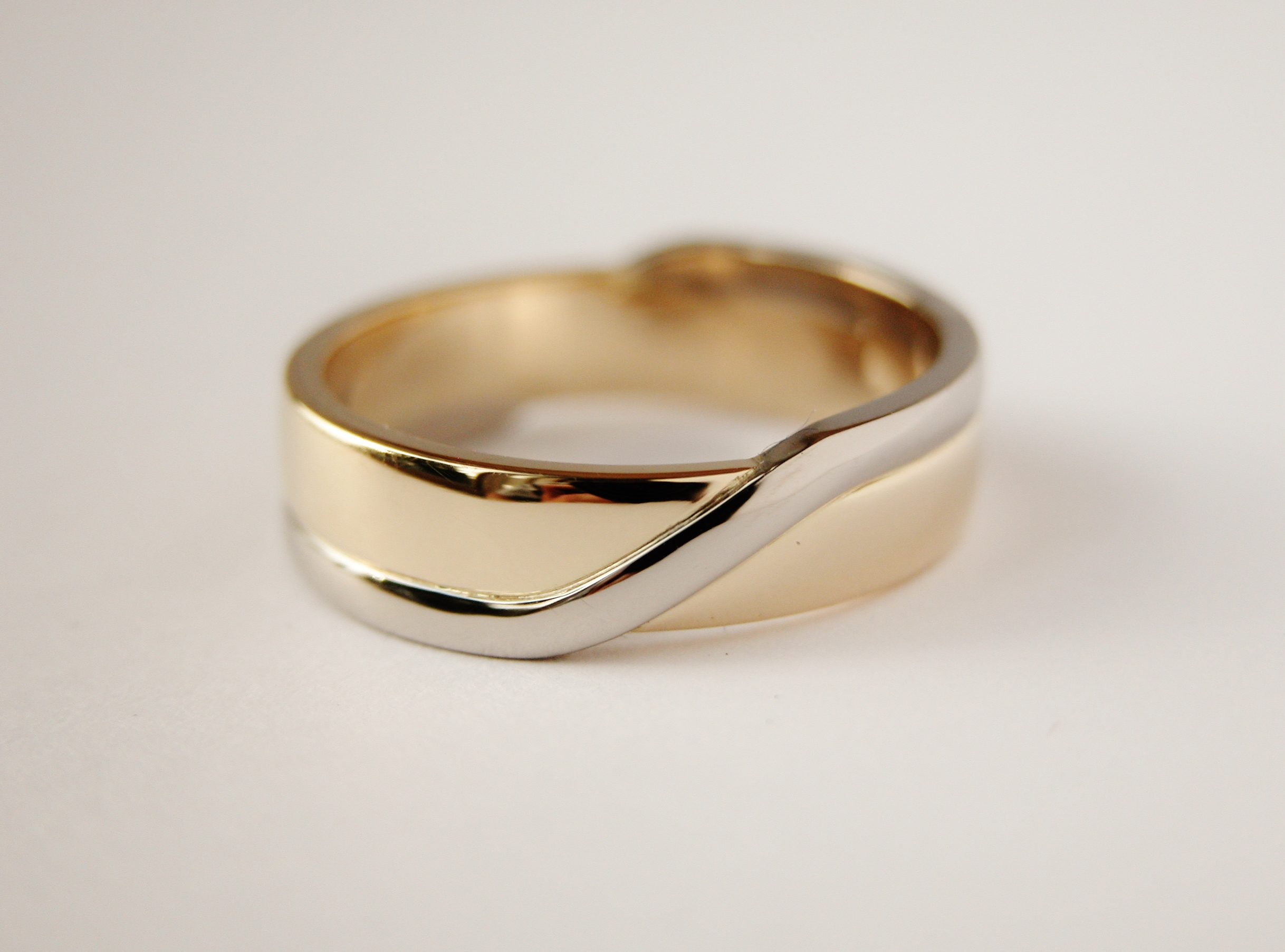 Gents 2 tone 9ct. yellow gold wedding ring with broad palladium wire applied & inlayed around edges & crossing over diagonally on the top and underside.