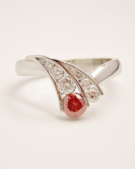 Pink round brilliant cut diamond weighing 0.29cts. channel set with 8 round white diamonds tapering in size in a curvy wishbone style platinum ring.