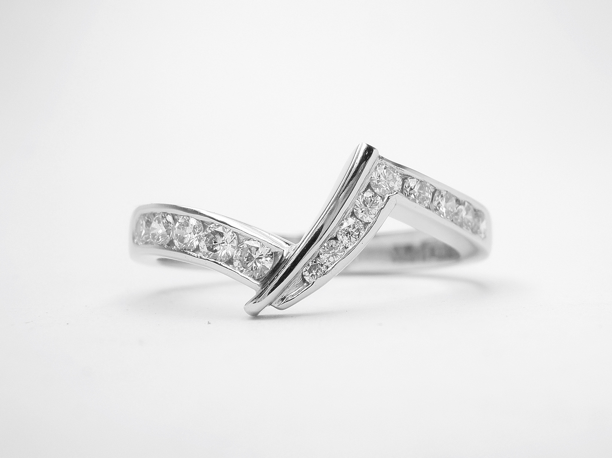 Platinum zig-zag wedding ring shaped to fit a pear shaped cross-over engagement ring, channel set with brilliant cut diamonds to 45% cover. This would also suite a marquise cross-over.