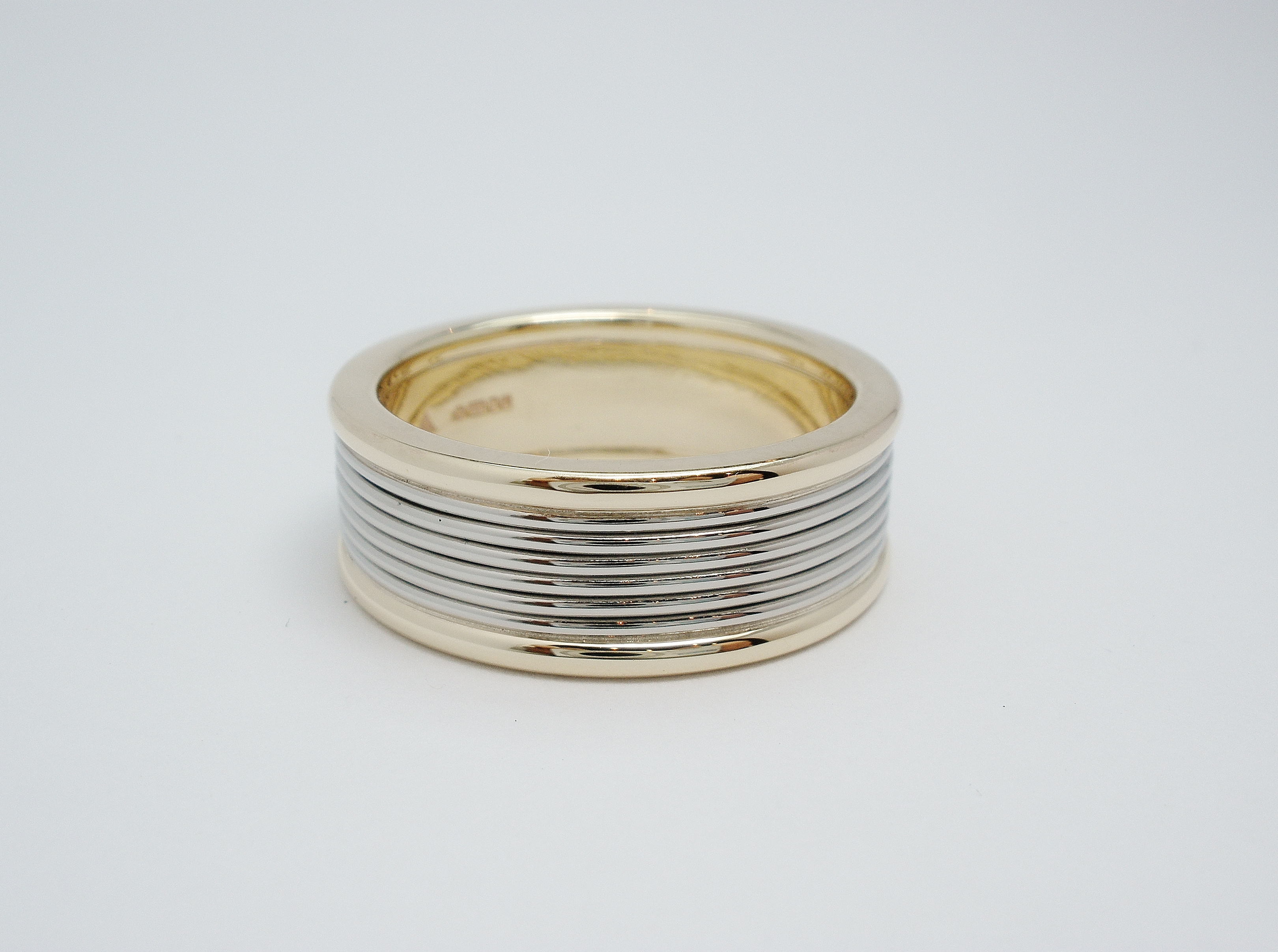 Platinum & 18ct. yellow gold gents 2 tone wedding ring with 18ct. yellow gold raised outer edge wires with a central platinum wire 'coil' effect.