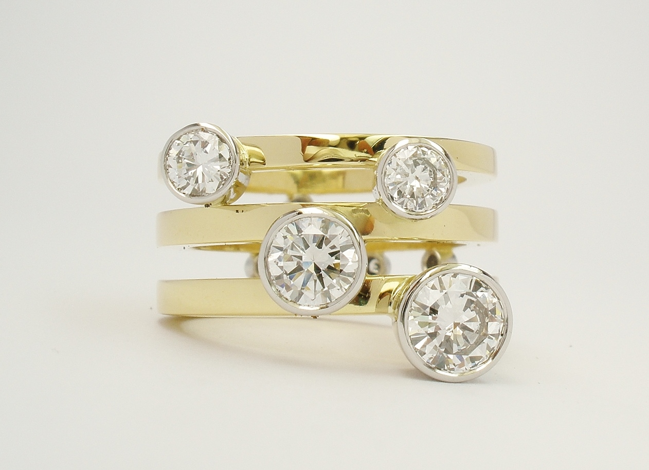 Round brilliant cut diamond 4 stone platinum rub-over set ring with a triple parallel 18ct yellow gold banded ring shank set with small diamonds on reverse side of bands. Ideal for right hand.