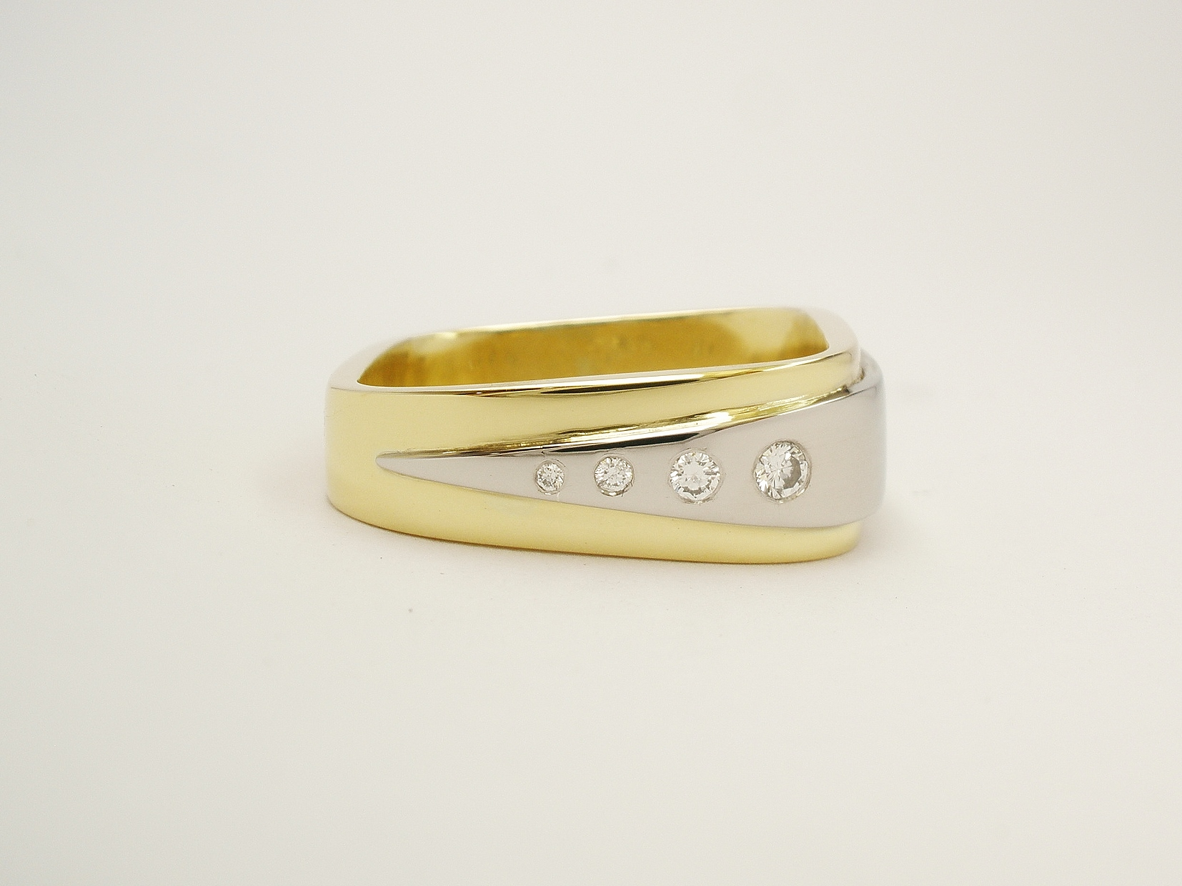 18ct. yellow gold 'wedge' shaped square ring overlaid with a wedge shaped platinum plate flush set with tapering sized round diamonds.