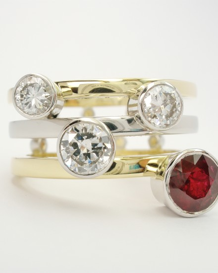 Round ruby & diamond 4 stone platinum rub-over set right handed ring with a triple paralell 18ct yellow gold & platinum banded ring shank set with small diamonds on reverse side of bands.