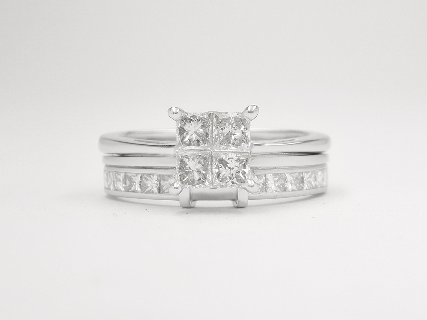 Palladium wedding ring shaped to fit 4 stone princess cut cluster engagement ring, & channel set with princess cut diamonds on either side of raised wires shaped to let in cluster.