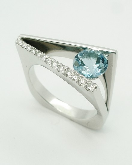 Round aquamarine & diamond 'Wedge' shaped, plateau, square sectioned ring mounted in palladium.