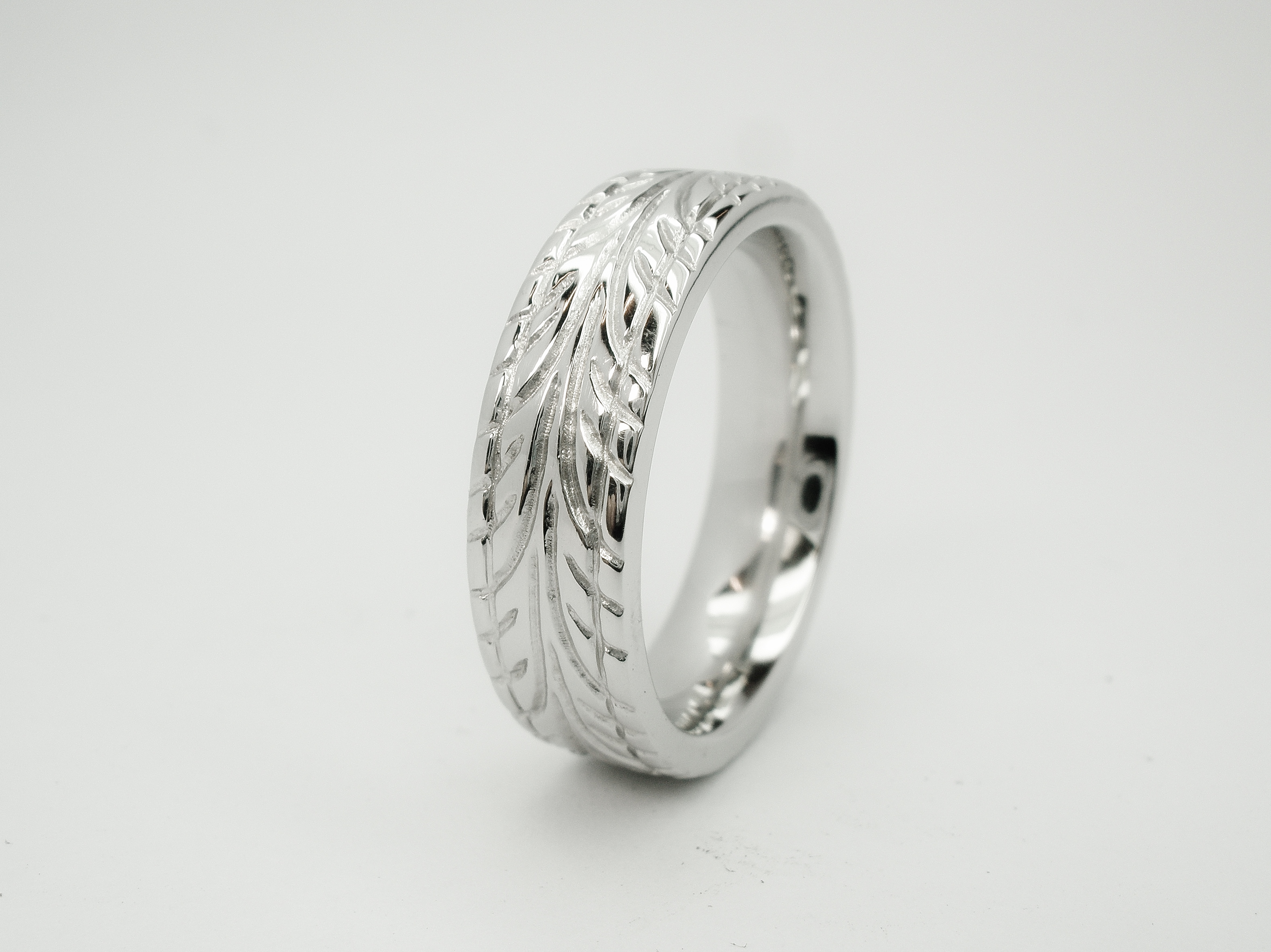 Gents platinum heavy sectioned flat court wedding ring, the cross section to mimic a low profile car tyre with a tyre tread pattern carved around.