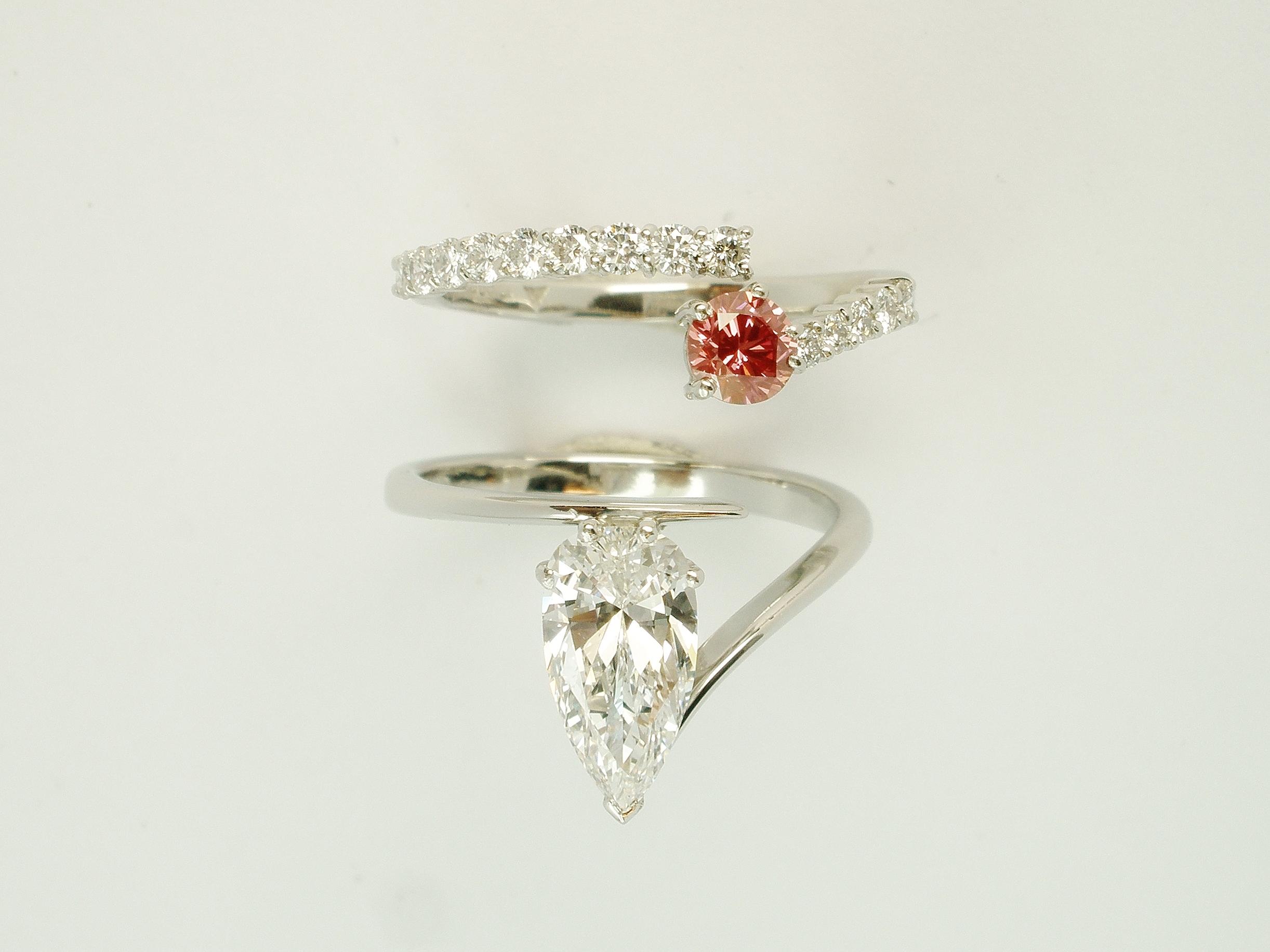 Pink round brilliant cut diamond & white diamond wire set platinum wedding ring shaped to interlock with a single diamond pear wishbone cross-over engagement ring.