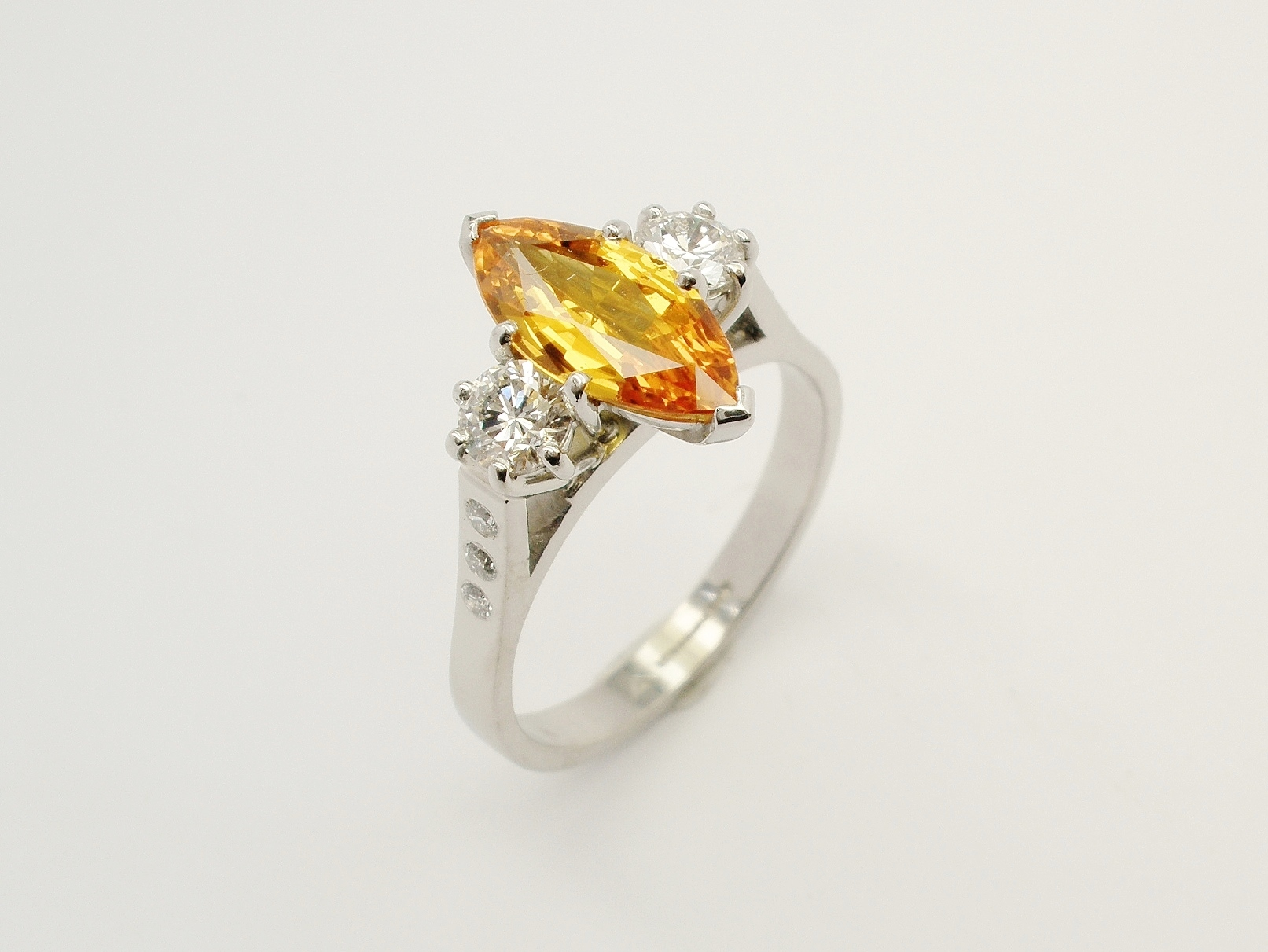 Orange marquise sapphire & round brilliant cut diamond 3 stone ring, mounted in platinum & palladium with diamond set shoulders.