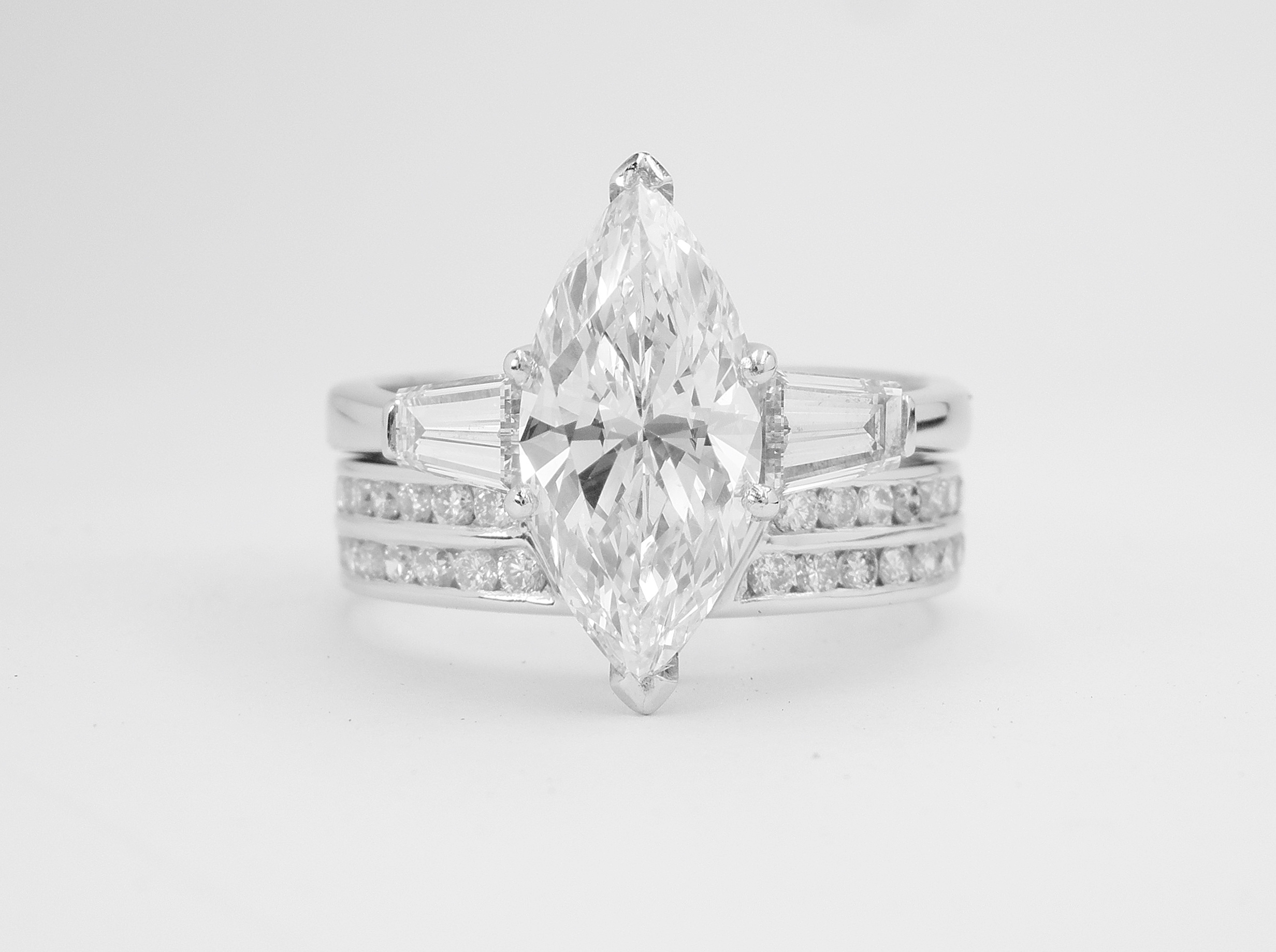 Double channel set round brilliant cut platinum wedding ring shaped with a fine 'V'shaped panel in centre to allow a diamond marquise ring with baguette shoulders to fit in.