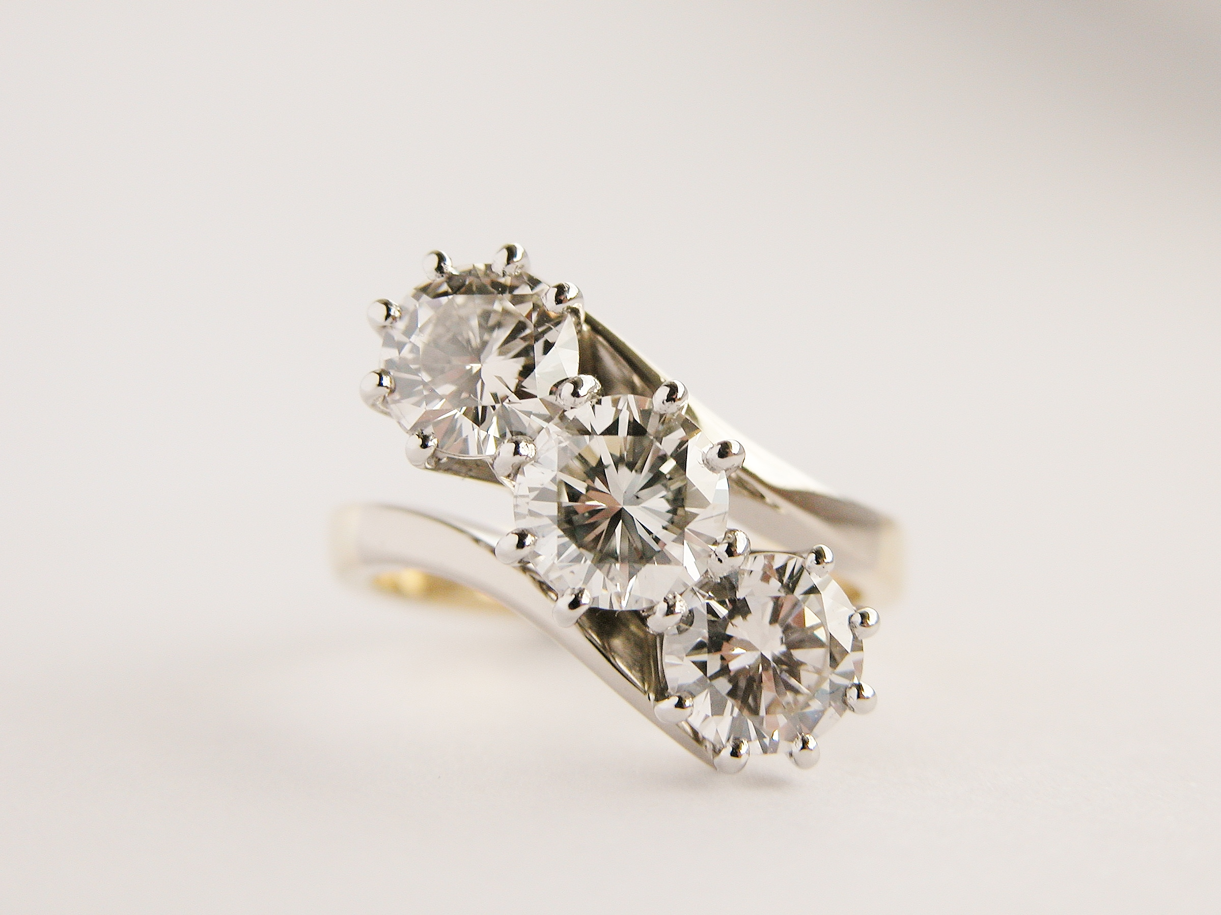 3 stone round brilliant cut diamond, straight cross-over style, right hand ring, mounted in 18ct. yellow gold and platinum.