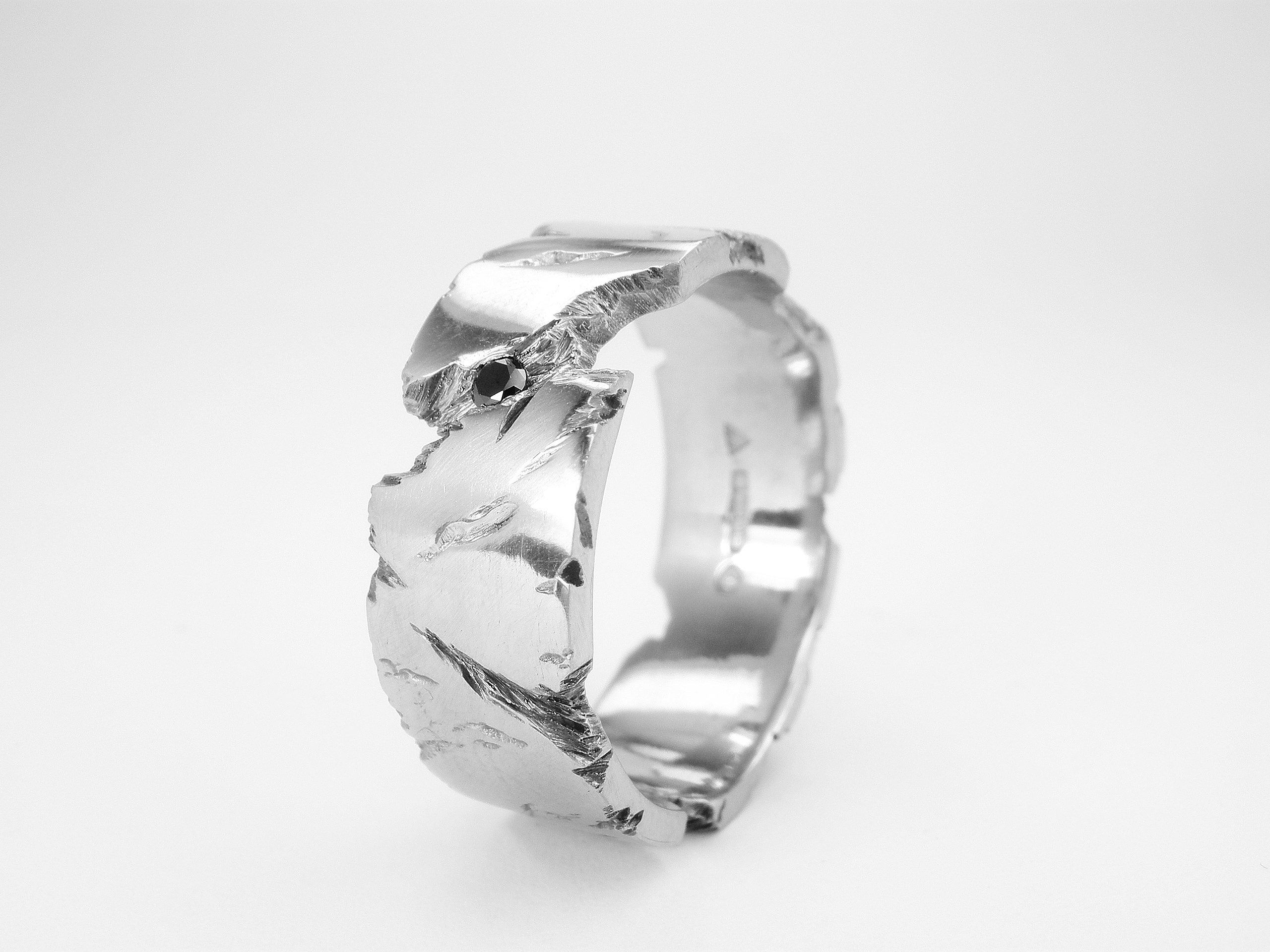 Palladium 'Fractured Rock' effect gents ring set with single black diamond & darkened in the recesses.