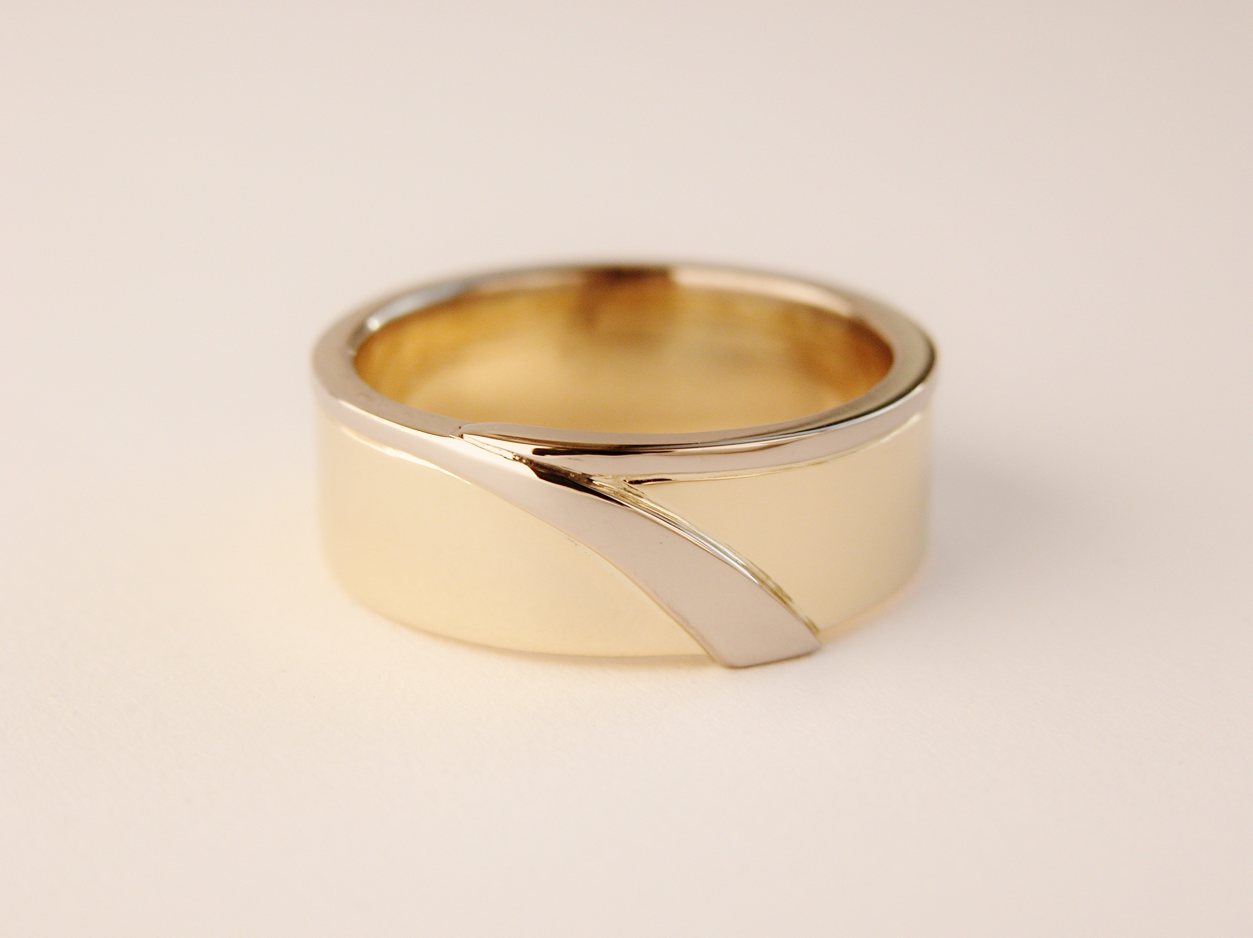 18ct. yellow gold Gents wedding ring with platinum wire attached around 1 edge extending to an inlayed flare.