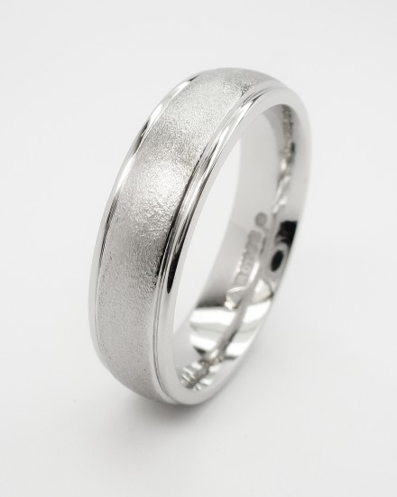 Gents platinum court sectioned wedding ring with a stipple finished centre and polished tram lines on edges.