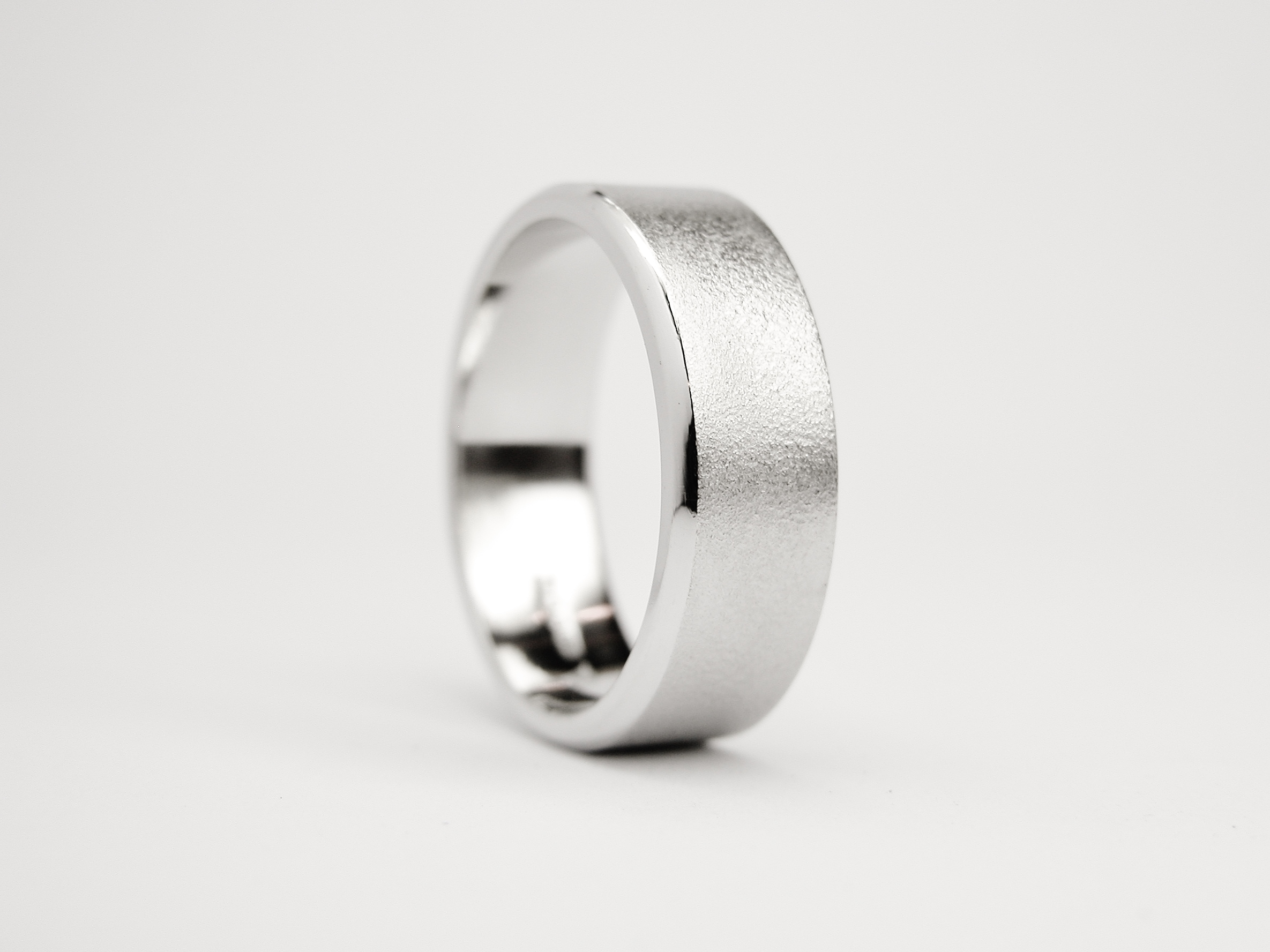 Gents palladium flat court sectioned wedding ring with a brushed finish & 1 polished bevelled edge and a darkened line cut inside the opposite edge.