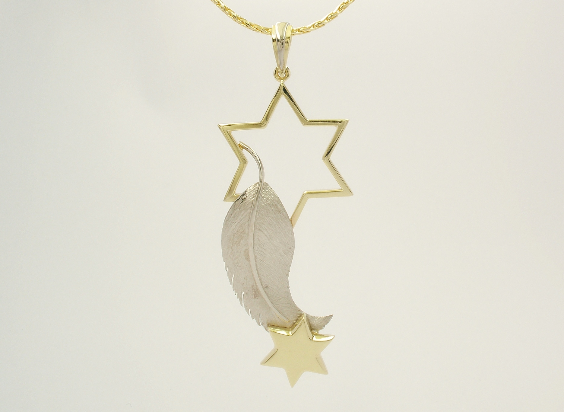 The design concept for this star and feather pendant was inspired from a significant event the client experienced a few days after her husband's death. Using her husband's wedding ring Alan was able to create both stars by rolling into sheet and wire. Palladium sheet was supplied to create the feather.
