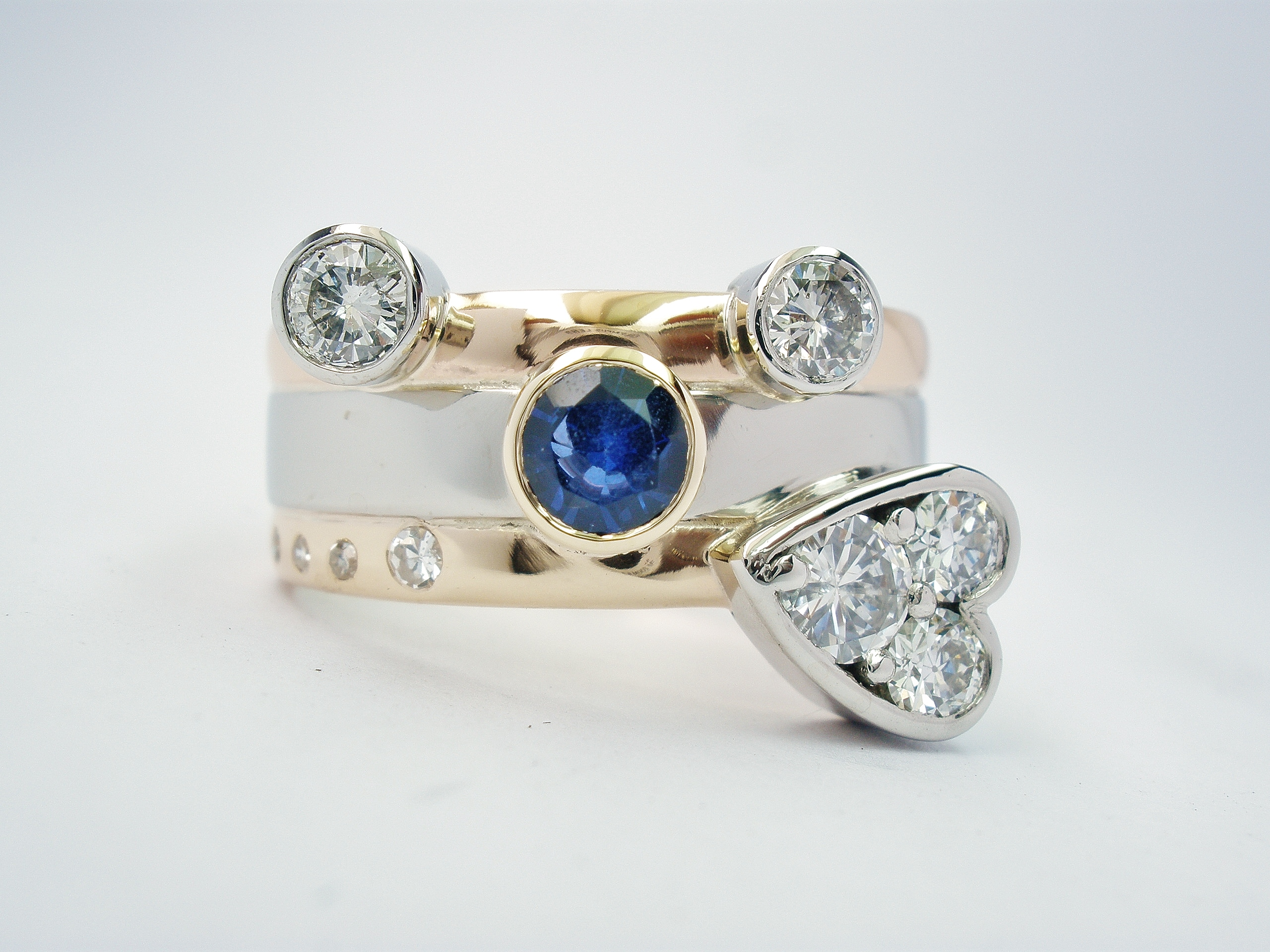 The clients brief was to include the 2 wedding rings, all the diamonds and the large sapphire and she wanted a heart shape somewhere on the ring.