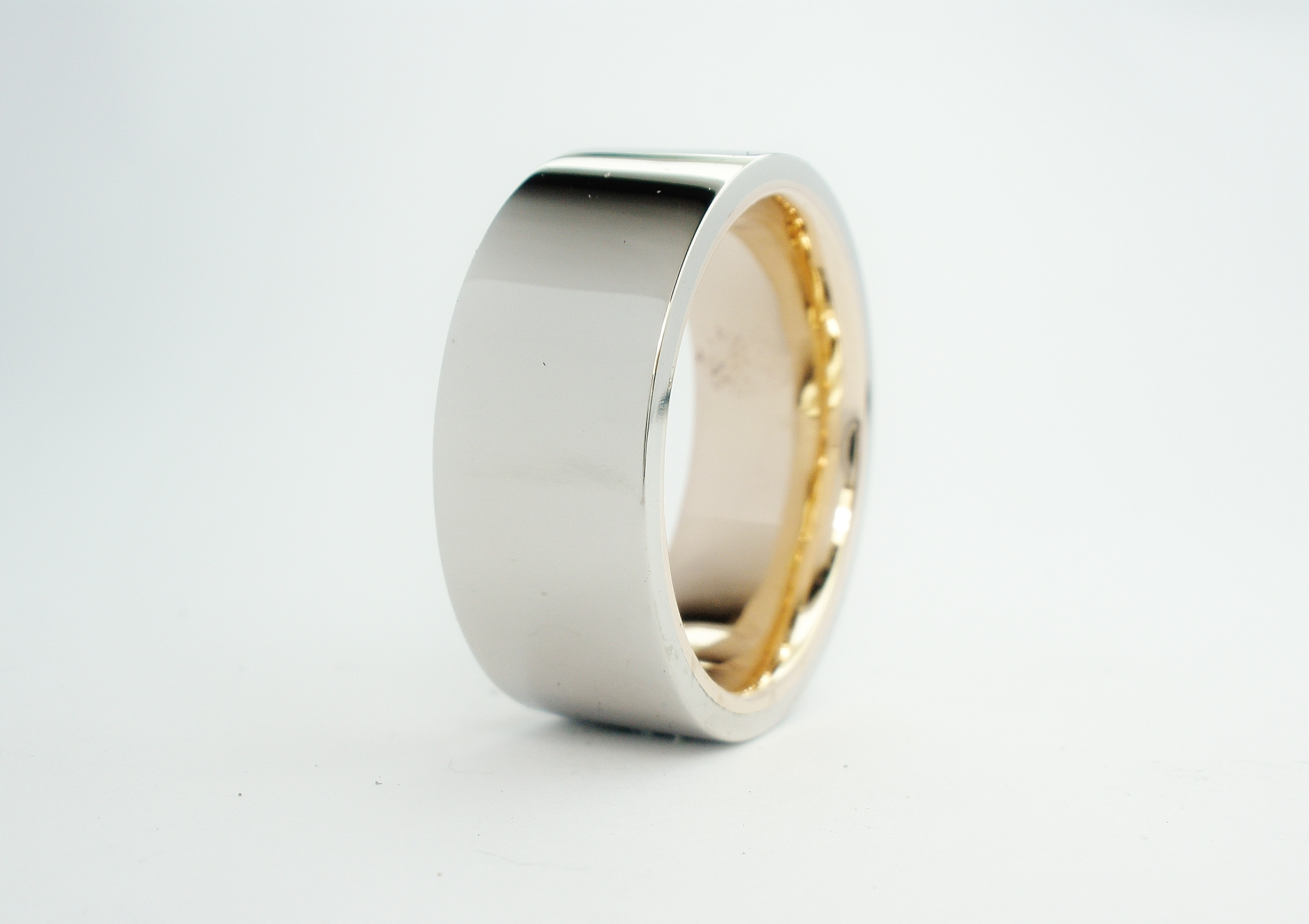 The gentleman had his father's 9ct. yellow gold wedding ring which he wished incorporated into his wedding ring which was to be visually white metal. The thickness and width of the father's ring allowed Alan to size the fathers ring to fit the client then overlay a palladium band. The 9ct yellow band is only visible when the ring is not being worn.