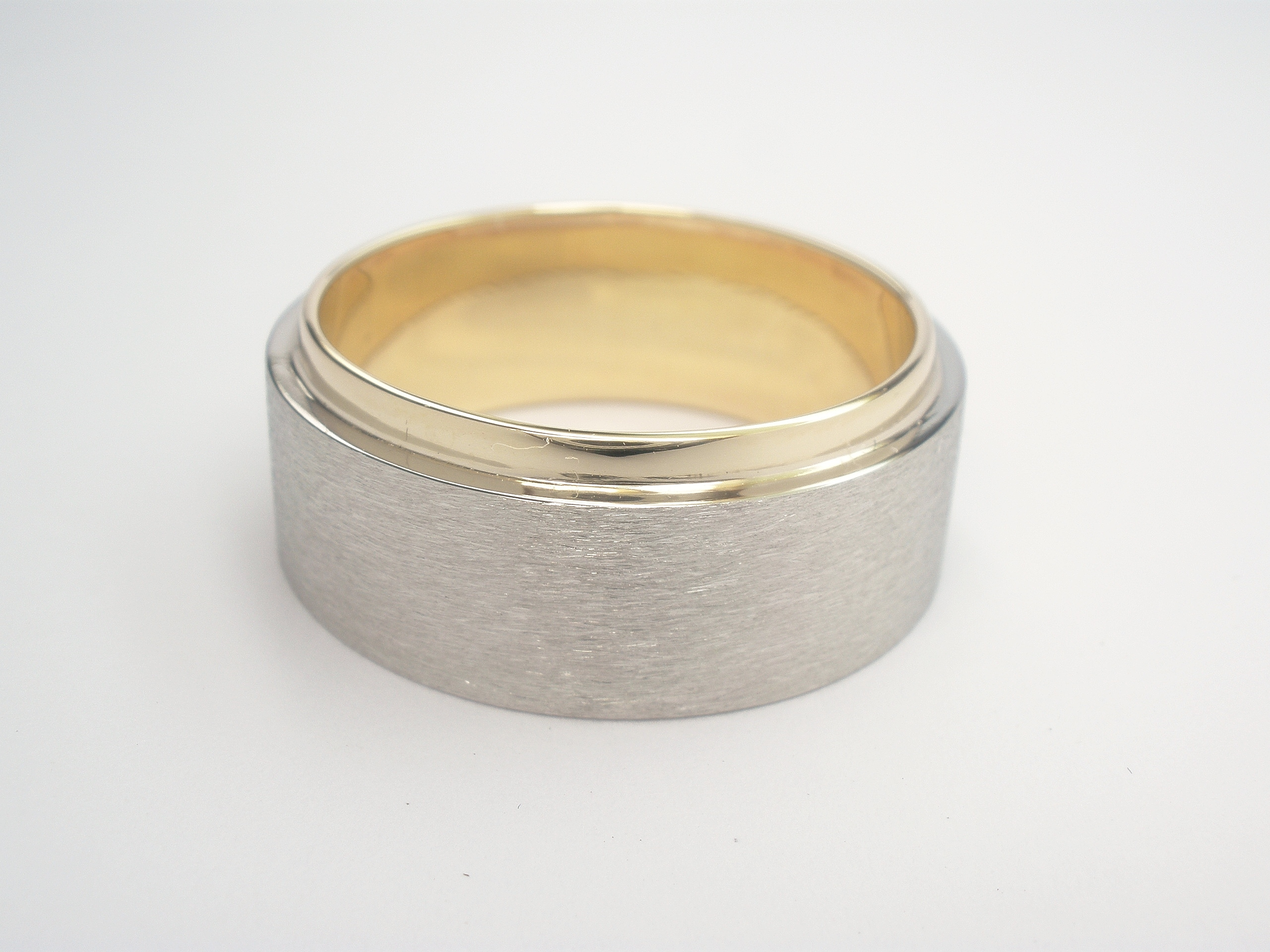 The gentleman had his father's 9ct. yellow gold wedding ring which he wished incorporated into his wedding ring although he wanted his ring to be predominantly white metal. Although the father's ring was very wide it suited the clients finger allowing Alan to size to fit then overlay a palladium band to 75% of the width allowing the 9ct. yellow gold inner ring to show.