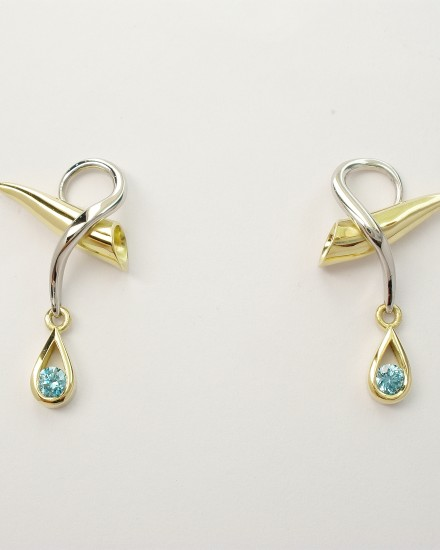 Round brilliant cut sky blue diamond set in a tear drop shaped 18ct. yellow gold setting hanging from an 18ct. yellow gold horn shaped stud and platinum wire loop.