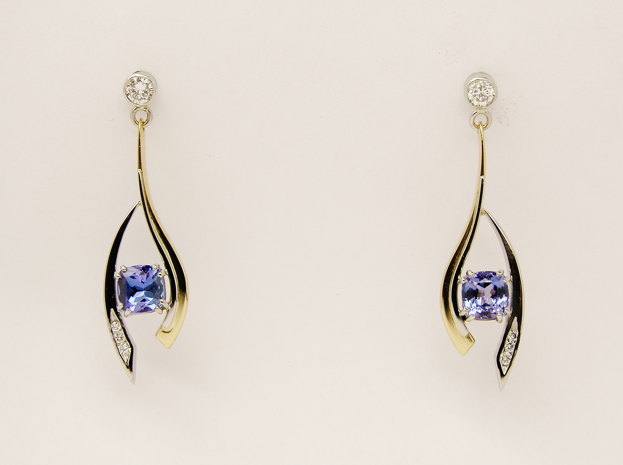 Cushion shaped Tanzanite and round brilliant cut diamond open pendulum earrings set in 18ct. yellow gold 2c palladium & platinum.