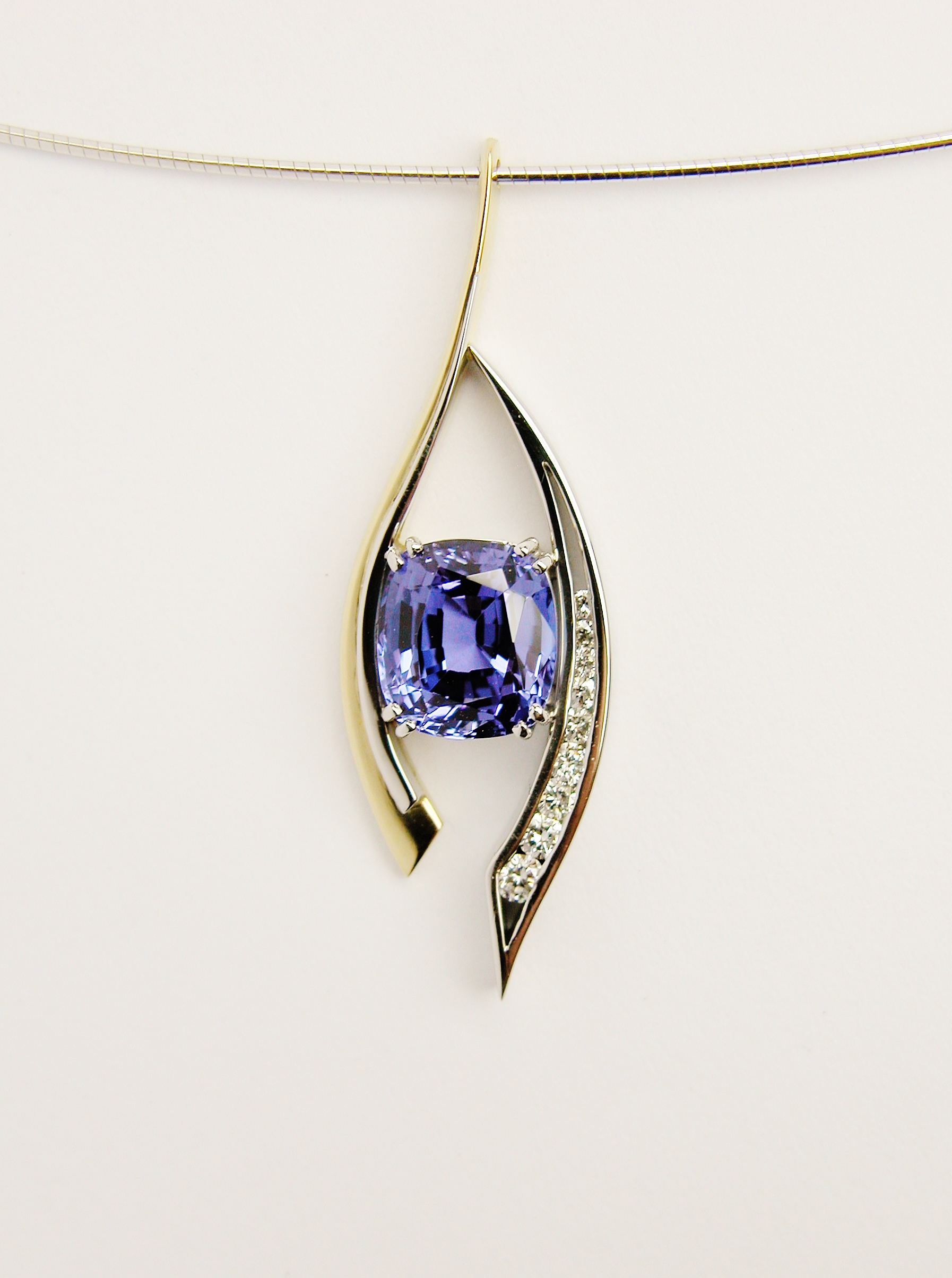 Cushion shaped Tanzanite and round brilliant cut diamond open pendulum pendant set in 18ct. yellow gold 2c palladium & platinum.