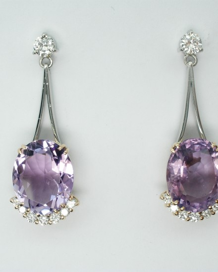 Oval amethyst and round brilliant cut diamond wishbone split wire pendulum style drop earrings.