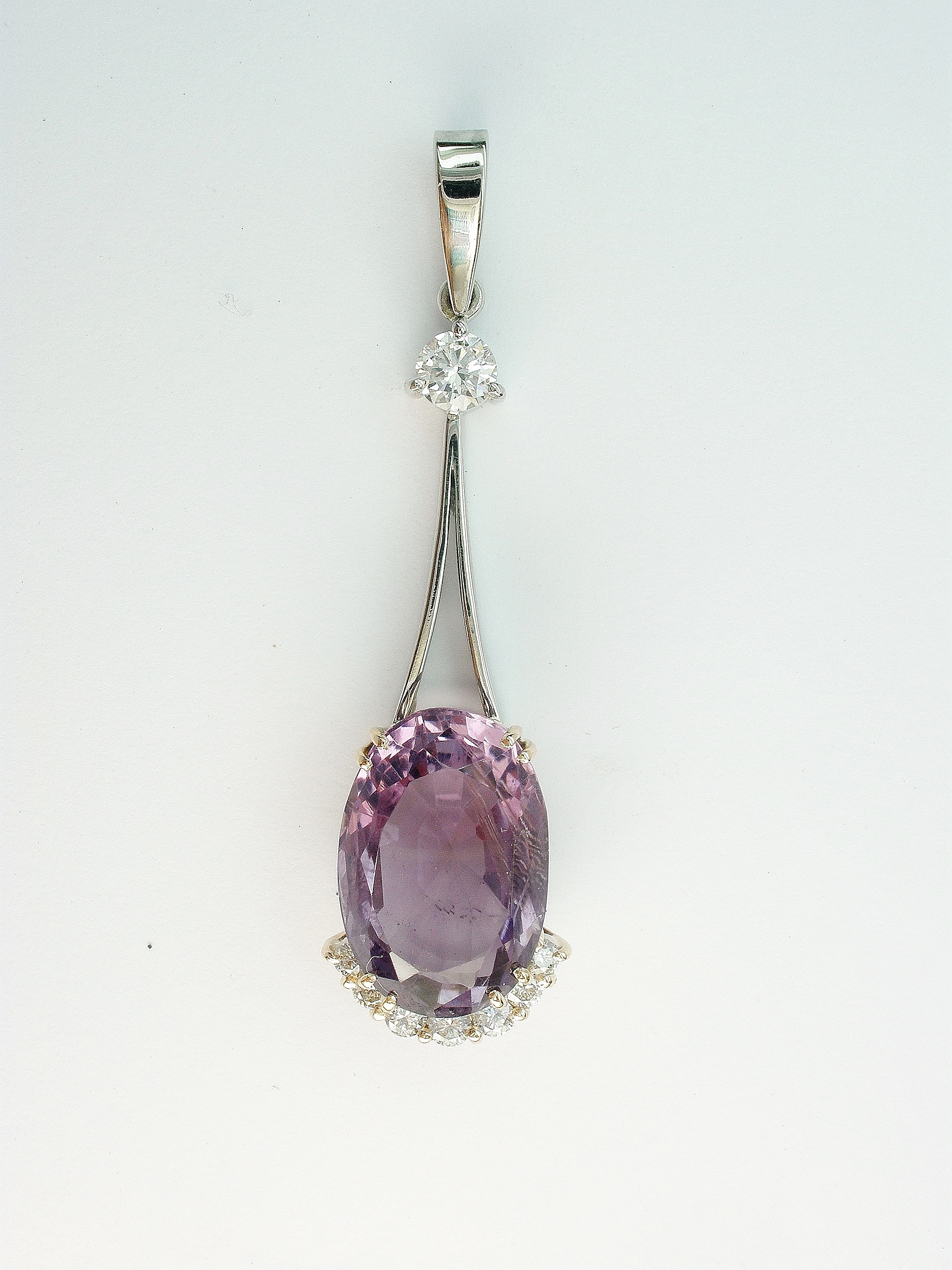 Oval amethyst and round brilliant cut diamond wishbone split wire pendulum style pendant.